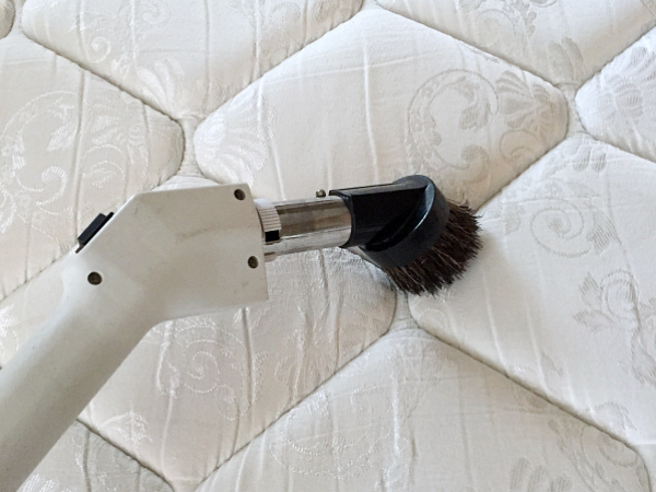 Vacuuming Mattress as part of the cleaning process