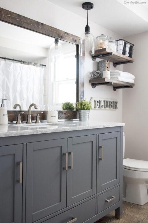 A framed mirror provides a farmhouse feel to the bathroom. Via Cherished Bliss.