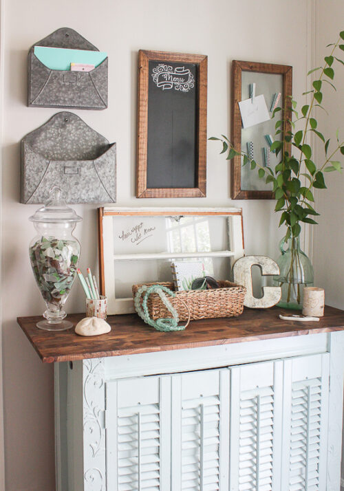 This command center idea come from Sand Dollar Lane and features a wood framed chalkboard, metal-style envelopes, and incorporates the use of a small shuttered table to display and old window and various knick-knacks.
