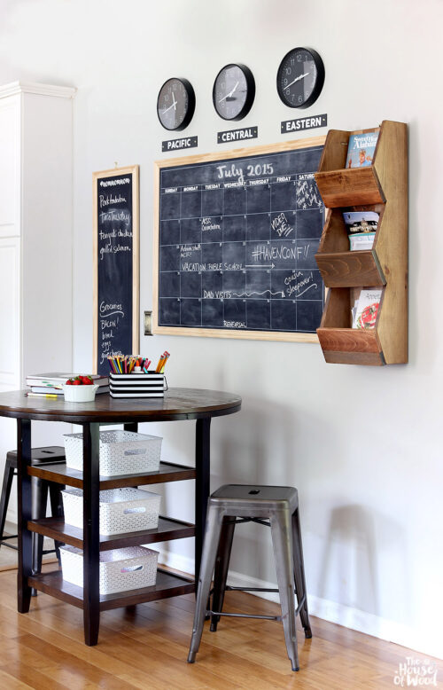 This command center was created by The House of Wood and features a large chalkboard calendar with clocks displaying the time in various time zones. It also has a three-tiered wooden bin to allow for books and magazines to be displayed.