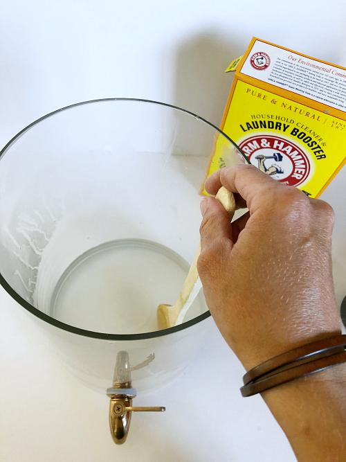 Stirring washing soda into hot water until dissolved