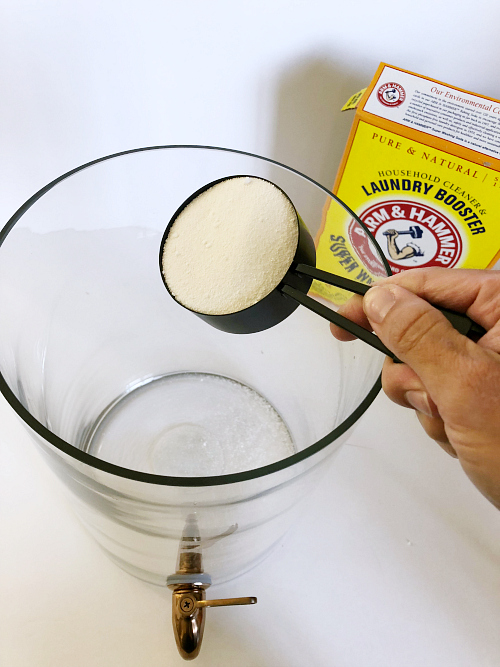 pouring washing soda into a drink dispenser to make DIY Thieves Laundry Detergent