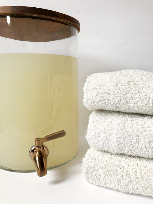 DIY Thieves Laundry Soap in a drink dispenser with folded white towels to the right. The DIY Thieves Laundry Detergent is free of harsh chemicals and costs less than $4/gallon. It's easy to make and smells amazing!