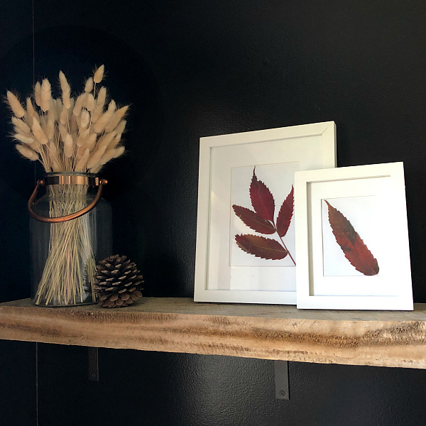 Wood Shelf is Bathroom with Framed Art made of fall leaves