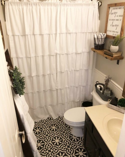 Gorgeous farmhouse bathroom with stenciled floor from Wilshire Collections.