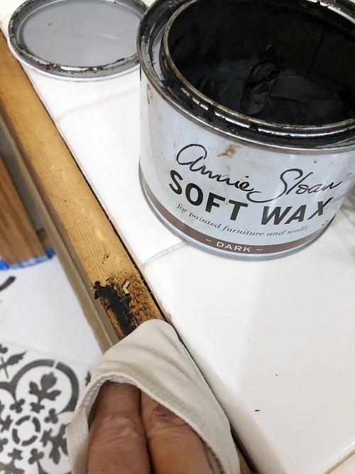 Applying dark wax to raw wood edge of tub surround