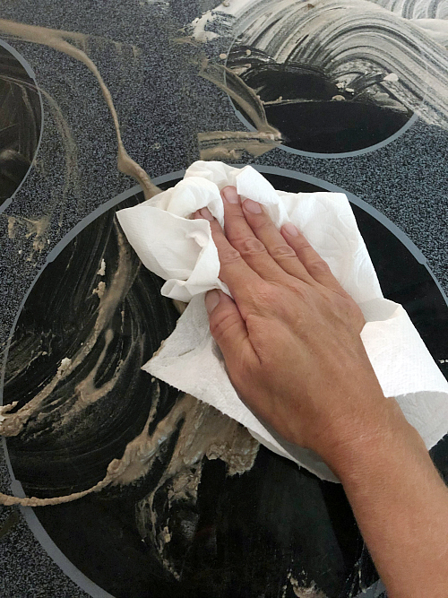 Cleaning A Glass Stove Top using paper towels to wipe clean