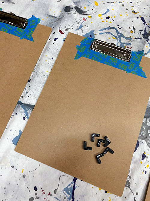 Applying painter's tape around clip of clipboard before applying a rusting solution.