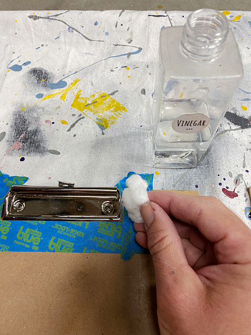 Applying vinegar to clip on clipboard in order to rust it.